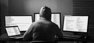 Person sitter foran dataskjermer